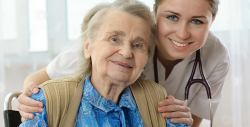 Lady hugging, from behind, an older lady in a wheelchair